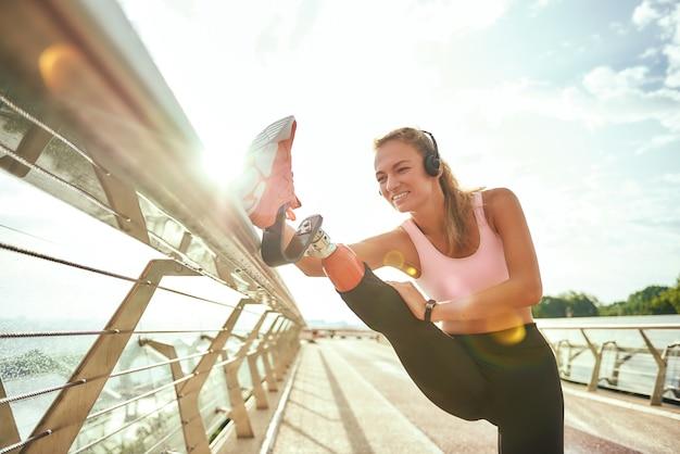 Donna positiva disabile in abiti sportivi e cuffie che allungano la gamba protesica mentre si sta in piedi sul