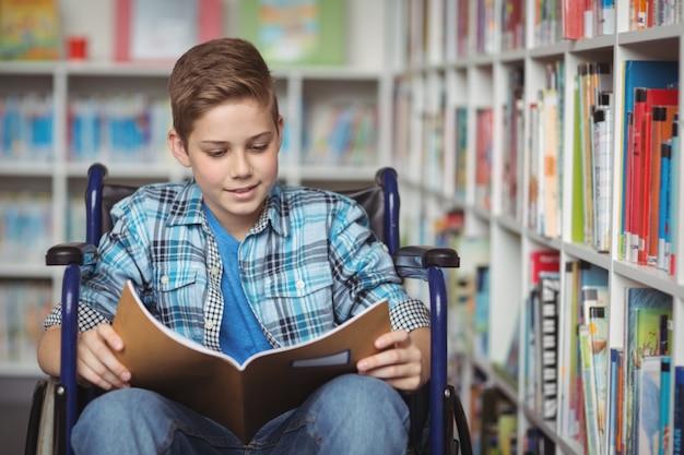 Libro di lettura di scolaro disabile in biblioteca
