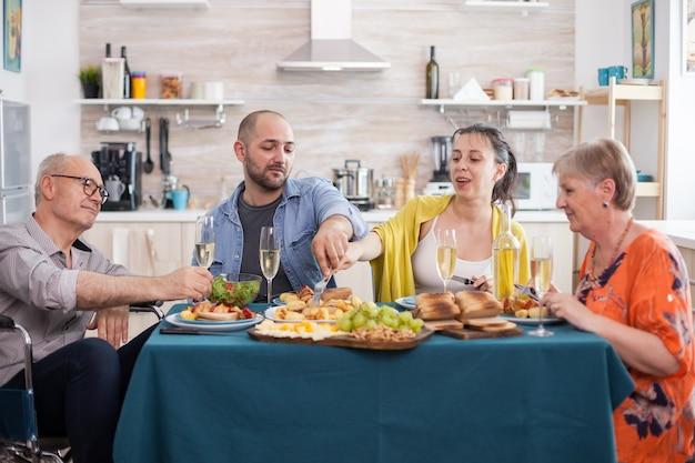 Uomo anziano disabile che tiene il bicchiere di vino durante il brunch con la famiglia in cucina. figlia felice durante il pranzo con fratello e genitori.
