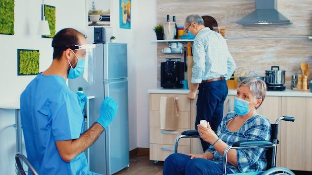 Donna anziana disabile in sedia a rotelle che tiene in mano una bottiglia di pillole dal caregiver con maschera facciale e visiera durante la pandemia di coronavirus. assistente sociale che offre pillole a una donna anziana handicappata. geriatra lui