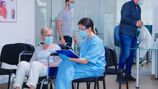 Donna anziana disabile in sedia a rotelle che parla con un'infermiera che indossa una maschera di protezione contro l'infezione da coronavirus. pazienti e personale medico in sala d'attesa. dottore in sala d'esame.