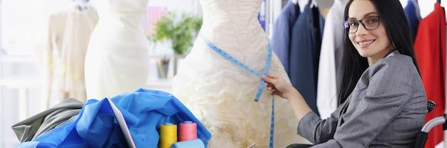La stilista donna disabile fornisce servizi per cucire abiti da sposa professioni per le persone