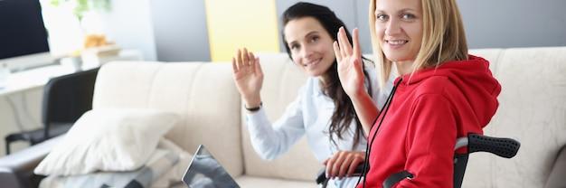 La donna disabile e l'amica sono sedute al laptop e salutano a casa
