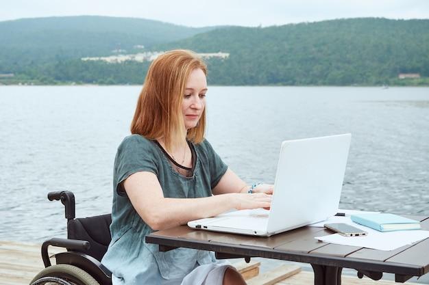 La donna disabile utilizza il computer portatile sullo sfondo della vista sul mare. concetto di lavoro a distanza, apprendimento