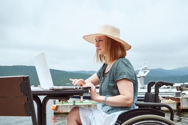 La donna disabile utilizza il computer portatile all'aperto. lavoro a distanza, concetto di apprendimento.