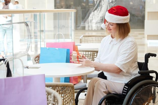 Una donna disabile che indossa un cappello da babbo natale con le borse della spesa