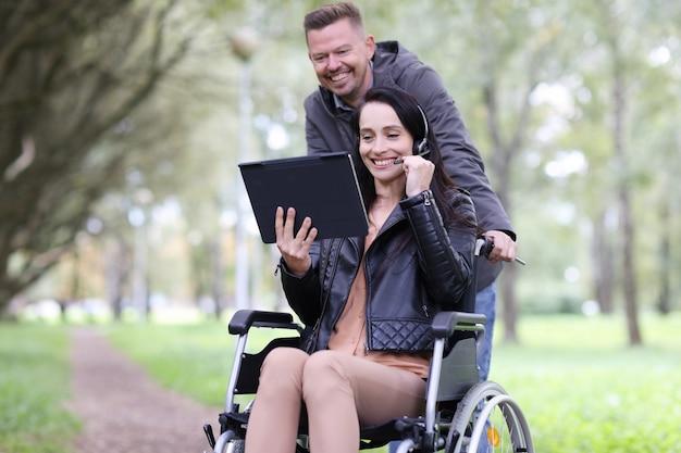 Donna disabile in sedia a rotelle e uomo che parla su tablet digitale nel lavoro a distanza del parco per le persone