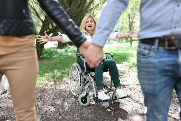 Donna disabile in sedia a rotelle che urla e piange di fronte a una coppia che lascia la sua relazione