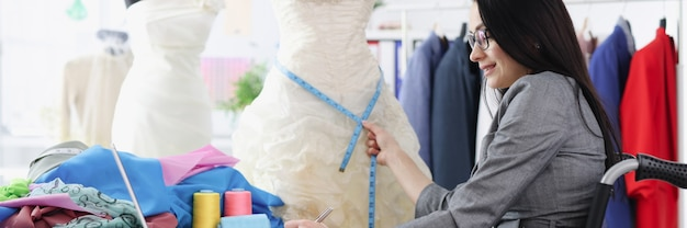 Donna disabile in sedia a rotelle che prende le misure dallo sviluppo del business dell'abito da sposa per