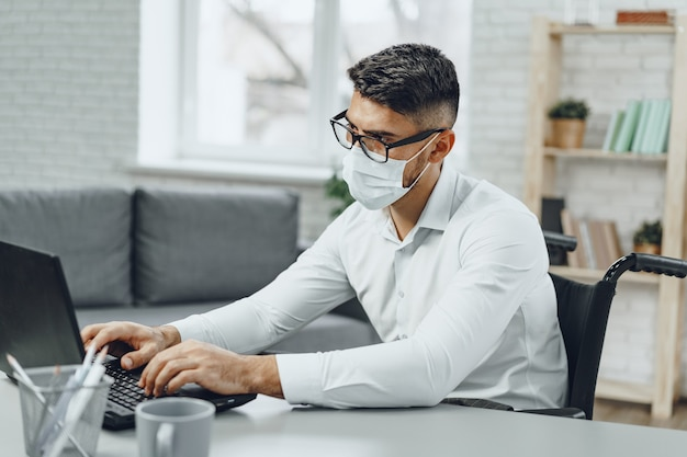 Disabili giovane imprenditore facendo il suo lavoro e indossando maschera facciale medica