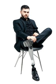 Giovane disabile con la gamba protesica, concetto dell'arto artificiale. seduto su una sedia, isolato