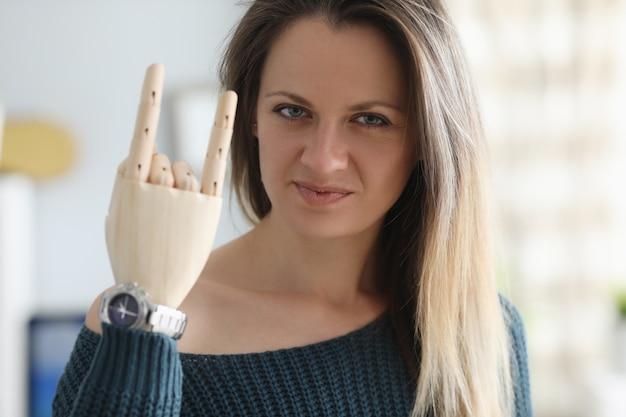 La giovane donna disabile mostra il ritratto di gesto della protesi dentaria in legno