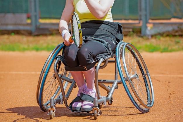 Giovane donna disabile su sedia a rotelle giocando a tennis sul campo da tennis.