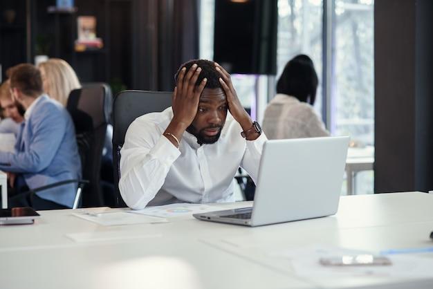 Responsabile di ufficio afroamericano deludente che guarda sullo schermo del computer portatile e mise le mani sulla testa al suo tavolo di lavoro sui precedenti dei colleghe.