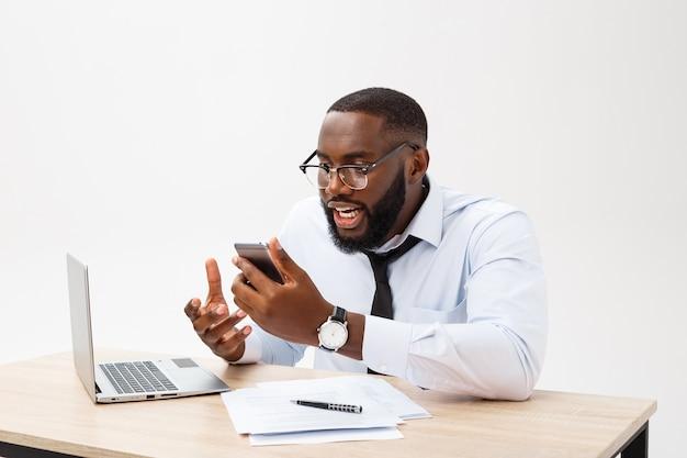 L'uomo d'affari africano deluso è stordito e confuso parlando al telefono.