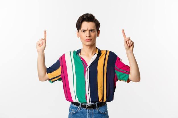 Uomo deluso e arrabbiato che punta il dito verso l'alto, mostrando qualcosa di brutto, in piedi su sfondo bianco. copia spazio