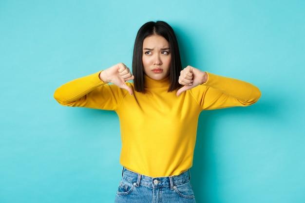 Donna asiatica delusa accigliata sconvolta, mostrando i pollici in giù in antipatia e disapprovazione, in piedi su sfondo blu, guardando a sinistra.