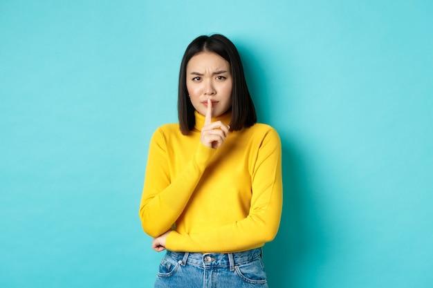 Donna asiatica delusa che dice di essere tranquilla, rimproverando la persona rumorosa con un gesto di silenzio, zitta davanti alla telecamera e accigliata sconvolta, in piedi su sfondo blu.