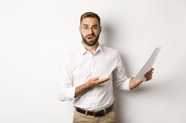 Capo deluso che rimprovera per cattiva relazione, indica documenti e sembra confuso, in piedi su sfondo bianco.