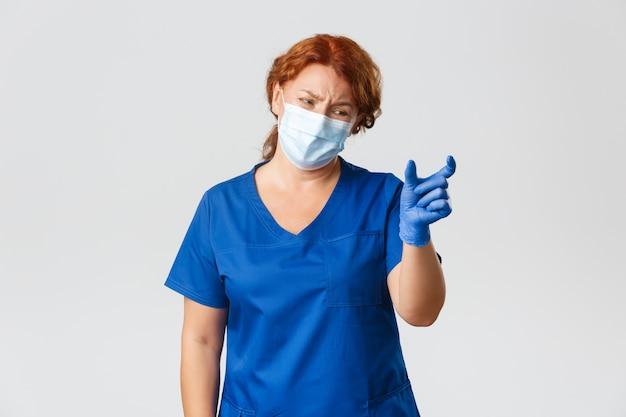 Dottoressa, infermiera o medico donna delusa e che si lamenta che mostra qualcosa di troppo piccolo e sembra dispiaciuta, indossa maschera e guanti.