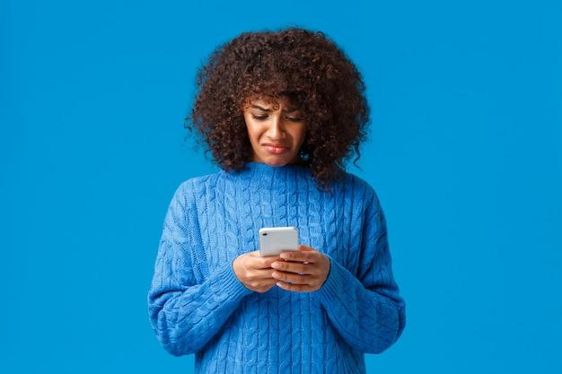 La donna afroamericana imbronciata e cupa delusa non ha l'umore natalizio, si sente a disagio a leggere il messaggio sconvolgente, sembra angosciata e triste allo schermo dello smartphone, parete blu