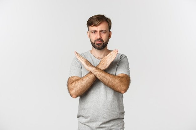 Uomo deluso con la barba, che mostra il gesto trasversale e accigliato