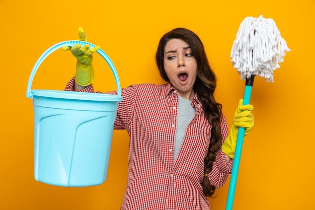 Donna delle pulizie piuttosto caucasica delusa con guanti di gomma che tengono mop e guardano il secchio