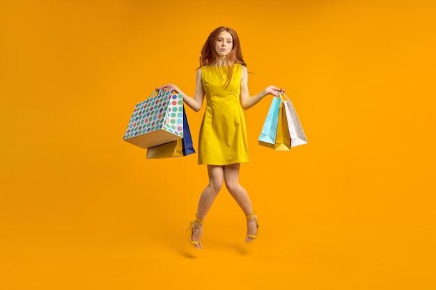 La donna dai capelli rossi delusa in abito tiene pacchetti per la spesa, sconvolta dallo shopping. la bella femmina sembra infelice, non ama l'acquisto. la donna annoiata e stanca compra regali, isolata su giallo, saltando