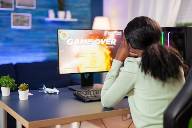 Donna africana triste delusa dopo aver perso la competizione di gioco online giocatore professionista arrabbiato che gioca durante un videogioco online sparatutto spaziale.