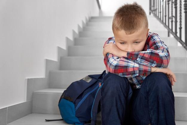 Scolaro deluso e triste della scuola primaria con lo zaino che si siede sulla tromba delle scale.