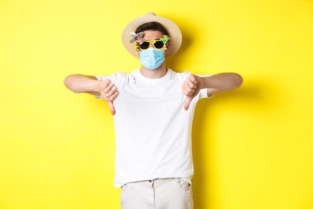 Turista deluso che si lamenta del blocco durante la pandemia, indossa una maschera medica e occhiali da sole, mostra il pollice verso il basso.