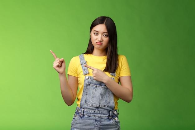 Delusa disinteressata ragazza asiatica cupa che punta il dito a sinistra facendo una smorfia imbronciata dispiaciuta...