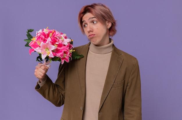 Deluso giovane bell'uomo che tiene e guarda un mazzo di fiori