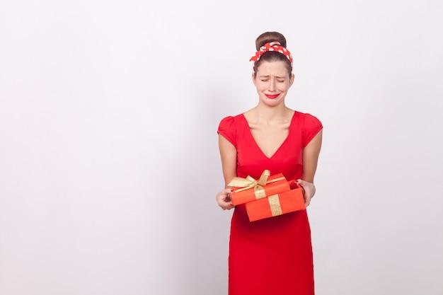 Delusione. donna che tiene scatola rossa e piangere. cattivo regalo. indoor, girato in studio, isolato su sfondo grigio