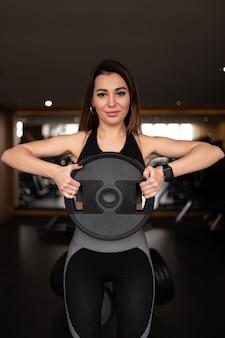 Un disco per bilanciere nelle mani di una donna the right young strength trainer