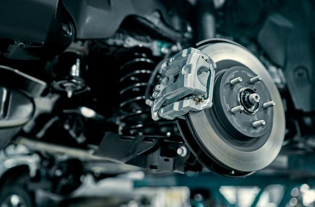 Freno a disco del veicolo per riparazione, in corso di sostituzione dei pneumatici nuovi. riparazione dei freni dell'auto in garage. sospensione dell'auto per la manutenzione dei freni e dei sistemi di ammortizzazione. primo piano.