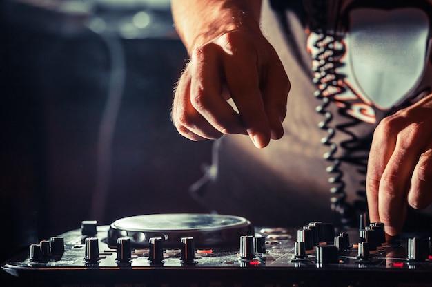 Disc jockey al giradischi dj suona sui migliori lettori cd famosi in discoteca durante la festa edm