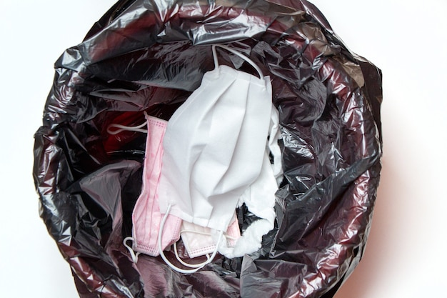 Guanti medici e maschere protettive scartati nel cestino della spazzatura dopo la quarantena