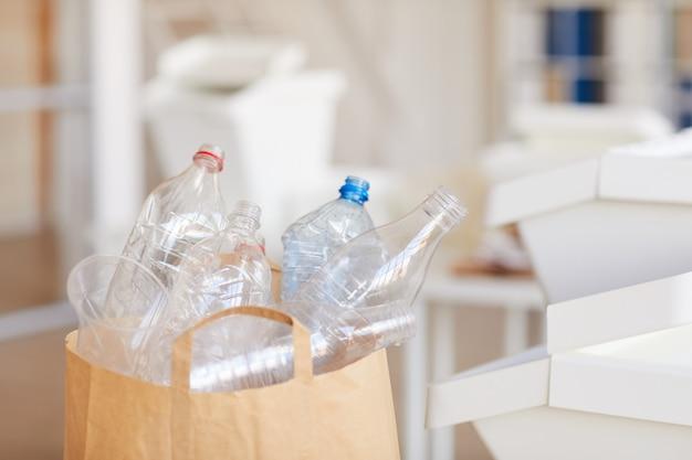 Bottiglie di plastica scartate in sacchetto di carta pronto per il riciclaggio in interni domestici