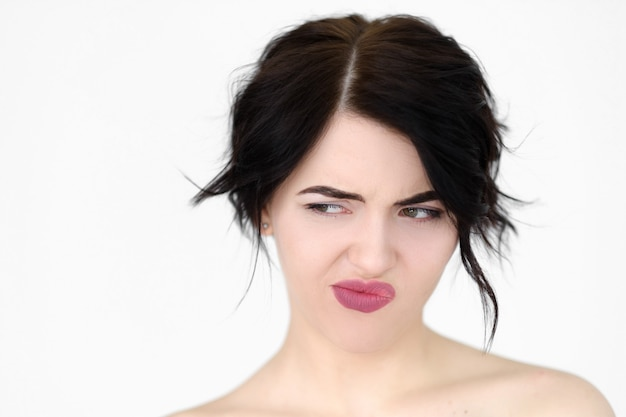 Malcontento donna invidiosa insoddisfatta che guarda lateralmente e pensa sul muro bianco.