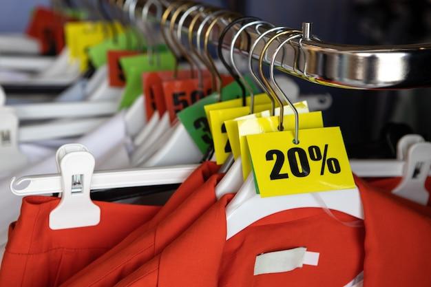 Etichette di vendita scontate, 20, 30, 50% di sconto, su grucce con vestiti in un negozio di abbigliamento casual. concetto di moda, stagione degli sconti, venerdì nero, shopping offline, espedienti, saldi natalizi.