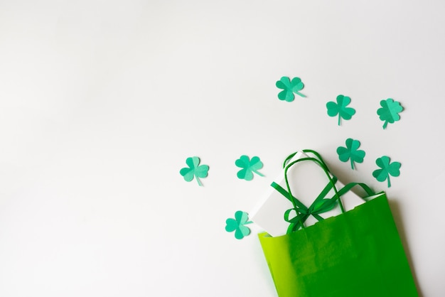 Sconti per il giorno di san patrizio. sacchetto di carta verde e foglie di trifoglio di carta, confezione regalo con un fiocco verde su sfondo bianco.