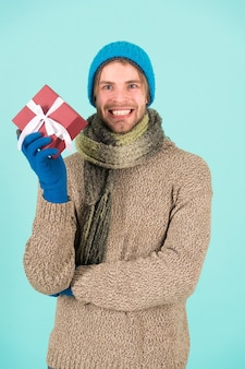 Scopri la bellezza dell'inverno. l'uomo tiene il regalo di natale. uomo felice in abiti invernali con scatola presente. l'inverno è nell'aria.