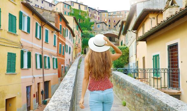 Alla scoperta dell'italia. vista posteriore di giovane donna attraente che cammina nella vecchia città italiana.