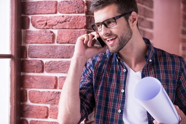 Discutere nuovo progetto architettonico. felice giovane uomo con gli occhiali che tiene il progetto e parla al telefono cellulare mentre sta in piedi al chiuso