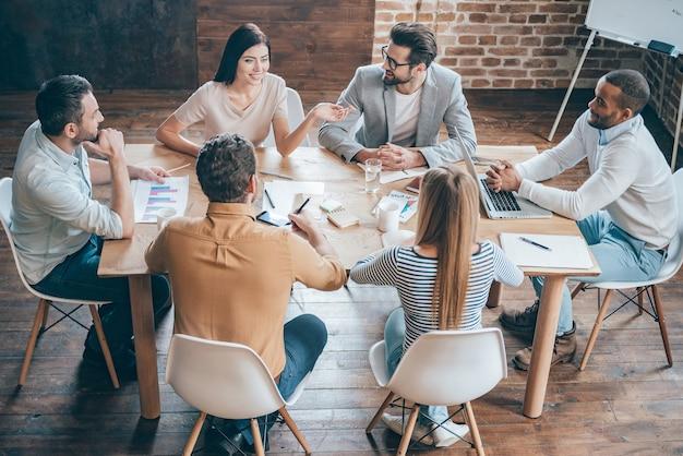 Discutere di nuove possibilità. vista dall'alto di giovani uomini d'affari che discutono di qualcosa mentre sono seduti insieme alla scrivania dell'ufficio