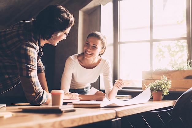 Discutere nuovo progetto. allegro giovane uomo e donna in abbigliamento casual che indica il progetto e comunica mentre entrambi in piedi vicino alla scrivania di legno in ufficio creativo creative