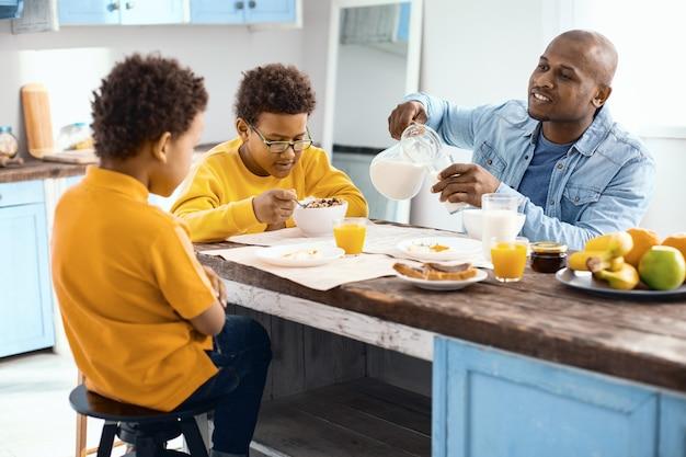 Discutere i piani. allegro giovane che versa un bicchiere di latte e chiacchiera con i suoi figli mentre fanno colazione in cucina