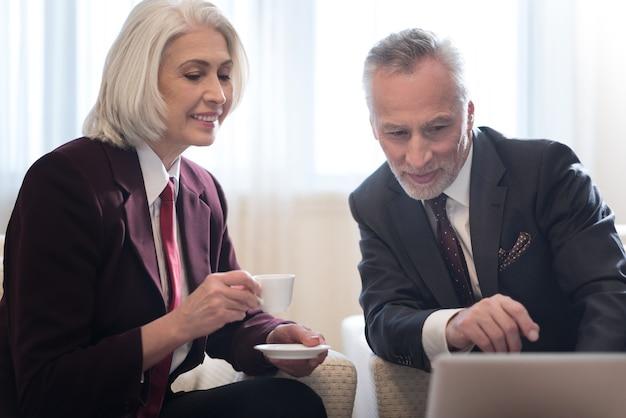 Discutere il progetto. sorridente barbuto uomo d'affari invecchiato guardando e indicando il laptop e seduto in hotel mentre si lavora al progetto con il suo collega ed esprime interesse