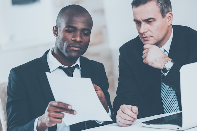 Discutere di un progetto. due uomini d'affari fiduciosi in abiti da cerimonia che discutono di qualcosa mentre uno di loro indica un foglio